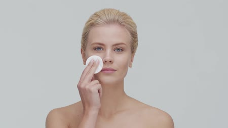 уход за кожей : Studio portrait of young, beautiful and natural blond woman applying skin care cream. Face lifting, cosmetics and make-up.