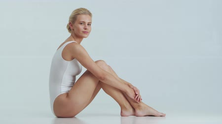 celulite : Young, beautiful, fit and natural blond woman in white swimsuit applying skincare cream. Massage, skin care, cellulite removal and weight loss.