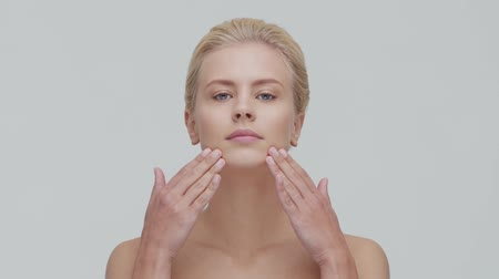 活性化させる : Studio portrait of young, beautiful and natural blond woman applying skin care cream. Face lifting, cosmetics and make-up.
