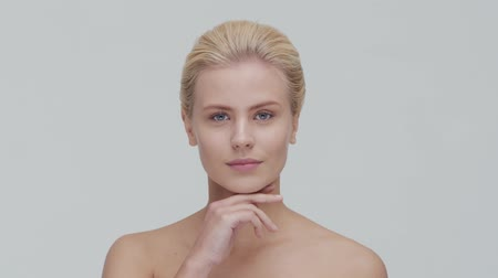 cuidados com a pele : Studio portrait of young, beautiful and natural blond woman applying skin care cream. Face lifting, cosmetics and make-up.