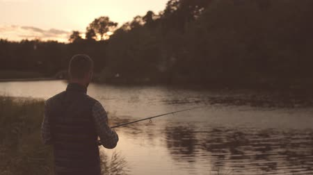 hegycsúcs : Fisherman with a spinning rod catching fish on a river. Fisher man on a weekend. Hobby, leisure and active summer and autumn concept.