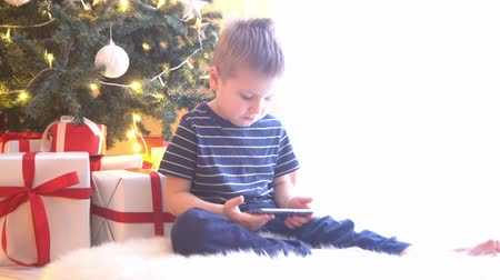 мультфильмы : Attractive little boy watching cartoons in front of Christmas tree with balls and lights. Kid preparing for the New Year at home.
