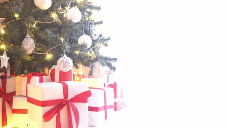 x mas : Beautiful Christmas tree decorated with balls and lights. Present boxes, gifts in front. Stock Footage