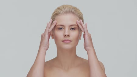 krem : Studio portrait of young, beautiful and natural blond woman applying skin care cream. Face lifting, cosmetics and make-up.