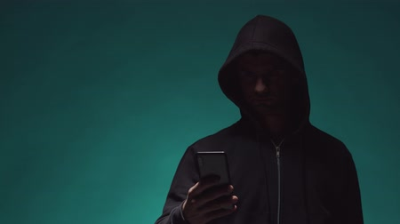 darknet : Portrait of computer hacker in hoodie. Obscured dark face. Data thief, internet fraud, darknet and cyber security . Stock Footage