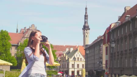 mirrorless : Attractive young girl traveling and exploring beautiful old town. Tourist with a retro camera.