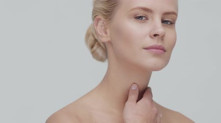 反 : Studio portrait of young, beautiful and natural blond woman applying skin care cream. Face lifting, cosmetics and make-up.