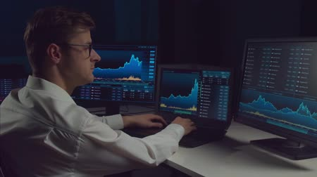 ワークステーション : Trader working in office at night using workstation and analysis technology. Stock markets, crypto currency, global business, financial trading and banking. 動画素材