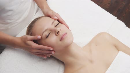 masszőr : Young, beautiful and healthy woman in spa salon. Traditional Thai massage therapy and skin care. Stock mozgókép