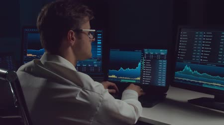 iş istasyonu : Trader working in office at night using workstation and analysis technology. Stock markets, crypto currency, global business, financial trading and banking. Stok Video