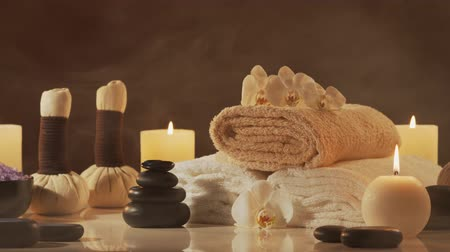 luz de velas : Aromatherapy, oriental massage and spa treatment. Relaxation composition of towels, candles, flowers, stones and herbal balls. Stock Footage