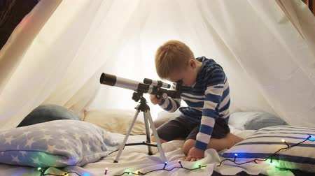 teleskop : Little boy playing with a telescope in childrens tent at home. Happy caucasian kid in the playroom. Stok Video