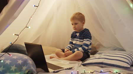 cosiness : Little boy playing in childrens tent at home. Happy caucasian kid in the playroom. Stock Footage