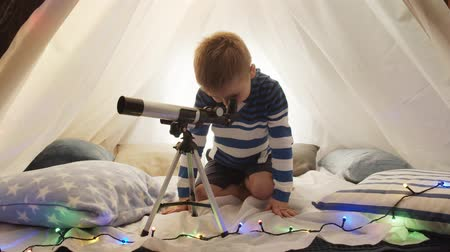 távcső : Little boy playing with a telescope in childrens tent at home. Happy caucasian kid in the playroom. Stock mozgókép