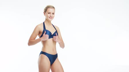 sports nutrition : Young, beautiful, fit and natural blond woman in blue swimsuit posing over isolated white background. Sport, fitness, skin care, cellulite removal, diet and weight loss. Stock Footage