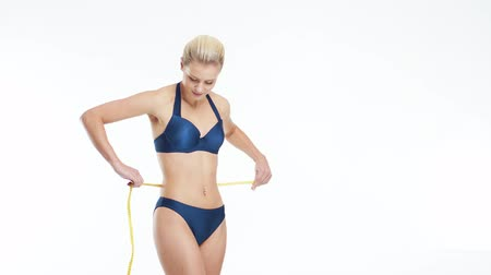 sports nutrition : Young, beautiful, fit and natural blond woman in blue swimsuit measuring her perfect body over isolated white background. Sport, fitness, skin care, cellulite removal, diet and weight loss.