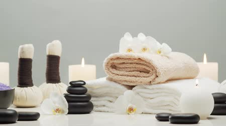 masaj : Aromatherapy, oriental massage and spa treatment. Relaxation composition of towels, candles, flowers, stones and herbal balls. Stok Video