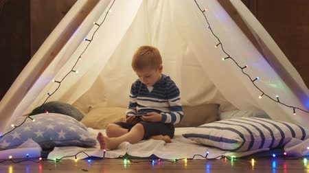 мультфильмы : Little boy playing in childrens tent at home. Happy caucasian kid in the playroom. Стоковые видеозаписи
