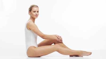 反 : Young, beautiful, slim and healthy blond girl in white swimsuit applying skincare cream. Massage, skincare, healthcare, wrinkles removal and fitness.