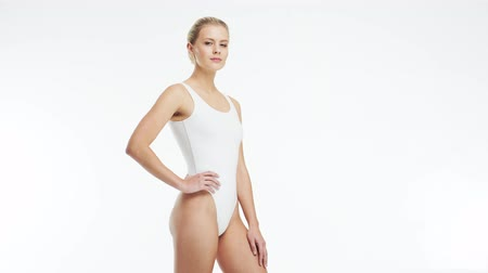 depilacja : Young, beautiful, fit and natural blond woman in white swimsuit applying moisturizing cream. Massage, skin care, cellulite removal, sport and weight loss.