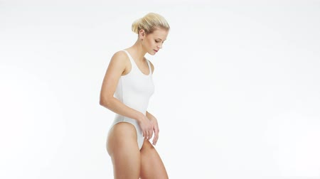 適用する : Young, beautiful, fit and natural blond woman in white swimsuit applying moisturizing cream. Massage, skin care, cellulite removal, sport and weight loss.
