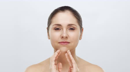 лицевой : Studio portrait of young, beautiful and natural blond woman applying skin care cream. Face lifting, cosmetics and make-up.