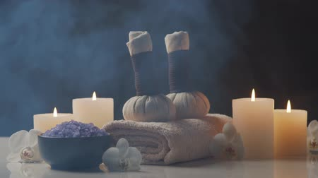 towel white : Aromatherapy, oriental massage and spa treatment. Relaxation composition of towels, candles, flowers, stones and herbal balls. Stock Footage