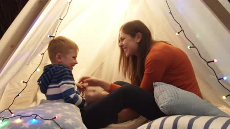 cosiness : Little boy playing playing with his mother in childrens tent at home. Happy caucasian kid in the playroom. Stock Footage