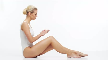 celulite : Young, beautiful, slim and healthy blond girl in white swimsuit applying skincare cream. Massage, skincare, healthcare, wrinkles removal and fitness.