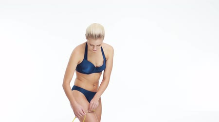 celulite : Young, beautiful, fit and natural blond woman in blue swimsuit measuring her perfect body over isolated white background. Sport, fitness, skin care, cellulite removal, diet and weight loss.