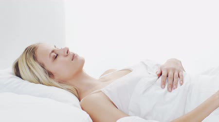 risveglio : Young woman lying in the bed. Beautiful blond sleeping girl. Morning in the bedroom. Health and rest concept.