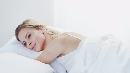 risveglio : Young woman in the bed. Beautiful blond girl wakes up. Morning in the bedroom, daylight from the window. Health and rest.