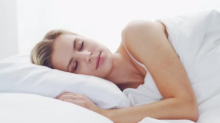 пробуждение : Young woman lying in the bed. Beautiful blond sleeping girl. Morning in the bedroom. Health and rest concept.