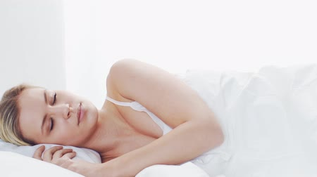 acorde : Young woman lying in the bed. Beautiful blond sleeping girl. Morning in the bedroom. Health and rest concept.