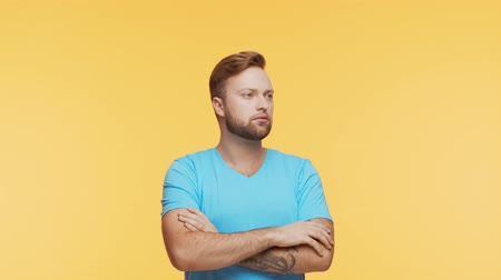 bras homme : Thinking young man over vibrant background. Studio portrait of expressive handsome person. Vidéos Libres De Droits