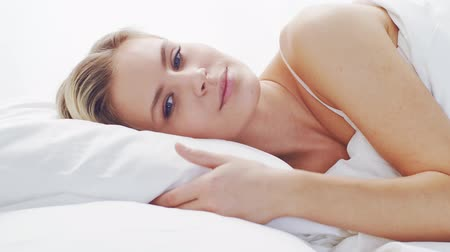 líný : Young woman in the bed. Beautiful blond girl wakes up. Morning in the bedroom, daylight from the window. Health and rest.