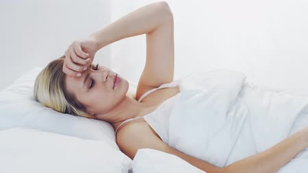procedimento : Young woman lying in the bed. Beautiful blond sleeping girl. Morning in the bedroom. Health and rest concept.