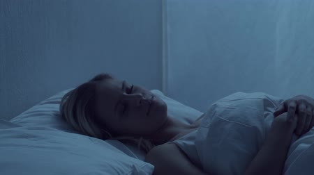 lidércnyomás : Young woman lying in the bed at night and having insomnia disease. Beautiful blond sleeping girl. Twilight in the bedroom, moonlight from the window. Sleeplessness concept. Stock mozgókép