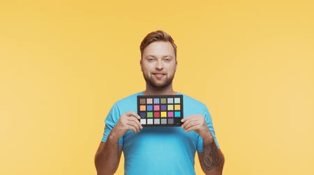 verificador : Expressive young man over vibrant background. Studio portrait of handsome person holding color checker. Coloristic and cinematography.