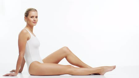 procedimento : Young, beautiful, fit and natural blond woman in white swimsuit applying moisturizing cream. Massage, skin care, cellulite removal, sport and weight loss.