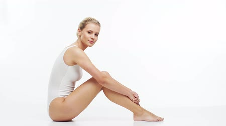 costumi da bagno : Young, beautiful, slim and healthy blond girl in white swimsuit applying skincare cream. Massage, skincare, healthcare, wrinkles removal and fitness.