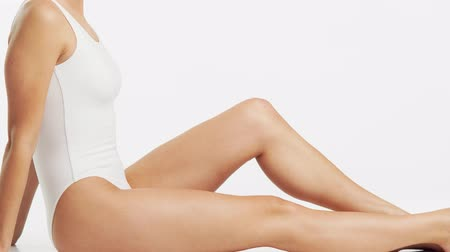 procedure : Young, beautiful, fit and natural woman in white swimsuit applying moisturizing cream. Massage, skin care, cellulite removal, sport and weight loss.