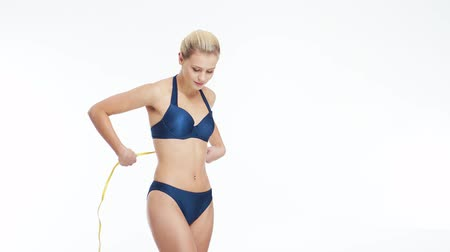 cuidados com o corpo : Young, beautiful, fit and natural blond woman in blue swimsuit measuring her perfect body over isolated white background. Sport, fitness, skin care, cellulite removal, diet and weight loss.