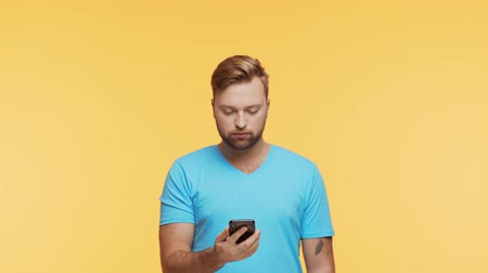 dialog : Expressive young man with a smartphone over vibrant background. Portrait of handsome person.
