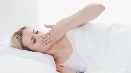 líný : Young woman lying in the bed. Beautiful blond sleeping girl. Morning in the bedroom. Health and rest concept.
