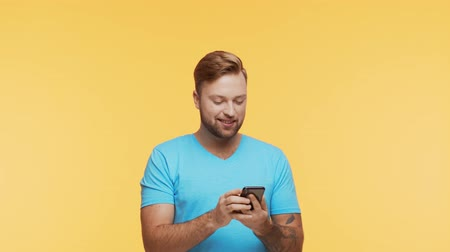 lezing : Expressive young man with a smartphone over vibrant background. Portrait of handsome person.