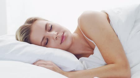 Young woman lying in the bed. Beautiful blond sleeping girl. Morning in the bedroom. Health and rest concept.