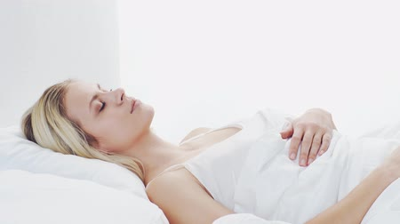 desperto : Young woman lying in the bed. Beautiful blond sleeping girl. Morning in the bedroom. Health and rest concept.