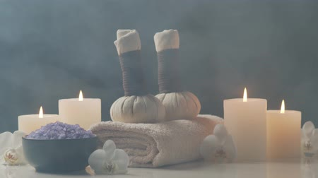 Oriental massage treatment composition. Towel, candles, flowers, stones and herbal balls. Spa procedures, meditation, wellbeing and aromatherapy. Стоковые видеозаписи
