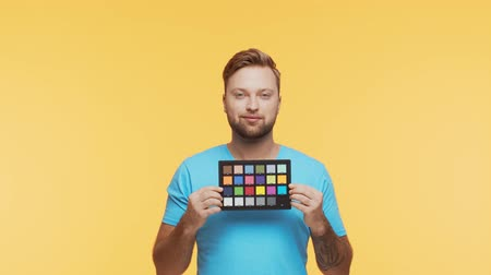 Expressive young man over vibrant background. Studio portrait of handsome person holding color checker. Coloristic and cinematography.